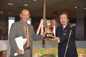 名倉組合長から優勝カップを受け取る勝野さん(左)
