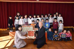 離島保育園の園児たちにトマトを贈る斉藤部会長(前列右)