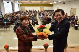 代表者に鉢花を手渡す名倉組合長(右)