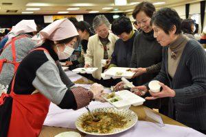 料理を盛り付ける女性部役員と参加者ら