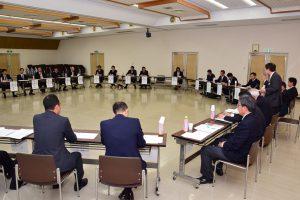 青年部員ら(画面奥)とJA役職員(手前)、立っているのはJAの名倉組合長