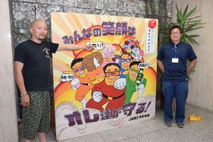 本店ホールに展示されたたて看板と斉藤部長(左)