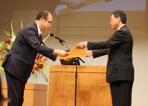 細田健一農林水産大臣政務官から表彰状を受け取ったJAの齋藤専務(右)