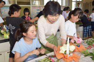 児童にアレンジフラワーを指導する生産者