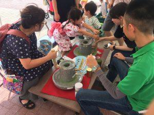 抹茶の石臼挽きを体験する参加者