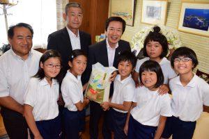 米を贈るJAの名倉組合長(後列中央)と佐久島小5・6年生の児童ら、佐久島小の黒柳校長(後列左2人目)、佐久島中の牧野校長(後列左端)