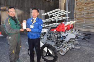 目録を手にするJAの浅井課長(右)と契約タマネギ研究会の尾崎会長(左)