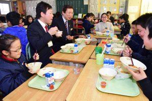 吉田小学校の児童と給食を楽しむ中村健市長(左2番目)とJAの名倉正裕組合長(左3番目)