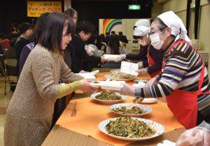 料理を盛り付ける女性部役員と参加者