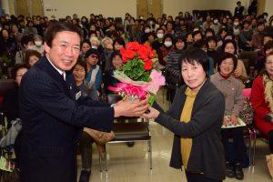 閉校式でJAの名倉組合長(左)から鉢花を贈られる代表者の広瀬さん(右)