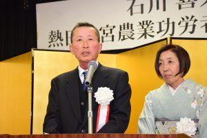 檀上で謝辞を述べる石川喜久雄さんと千賀子夫人