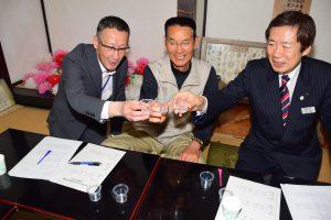 試作品の芋焼酎で乾杯するJAの名倉組合長(右)、島を美しくつくる会の鈴木代表(中央)、西尾市地域振興部の山﨑部長(左)