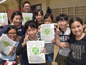 寄贈されたクリアファイルを手に笑顔の児童と制作に携わったJA職員の鈴木拳汰さん(奥)