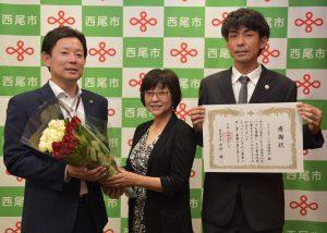 中村市長(左)に今週のバラを贈る若山事務長(中央)と感謝状を受け取った稲垣組合長(右)