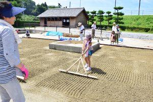 海水をまいた塩田の砂に筋を付ける参加者の子供ら