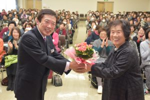 JAの名倉組合長からベゴニアの鉢花を贈られる、代表者の中根さん(右)