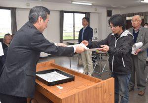 都築常務(左)から修了証書を受け取る大城さん(右)らいちじくスクール修了生