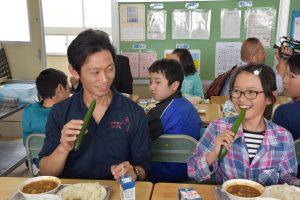 生産者とともにキュウリを食べる児童