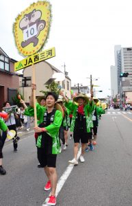 JAの看板を先頭に踊りを披露するJA職員チーム